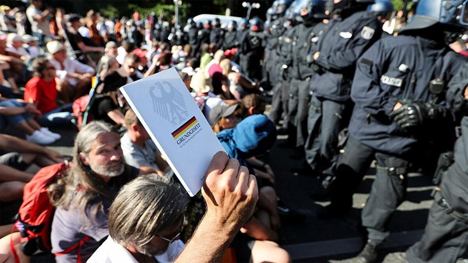 Германчууд 10 хүн тутмын нэг нь эрүүл ахуйн хязгаарлалтын эсрэг хандан, зарим нь гартаа үндсэн хуулиа барьж эсэргүүцлийн цуглаанд ирсэн байна.